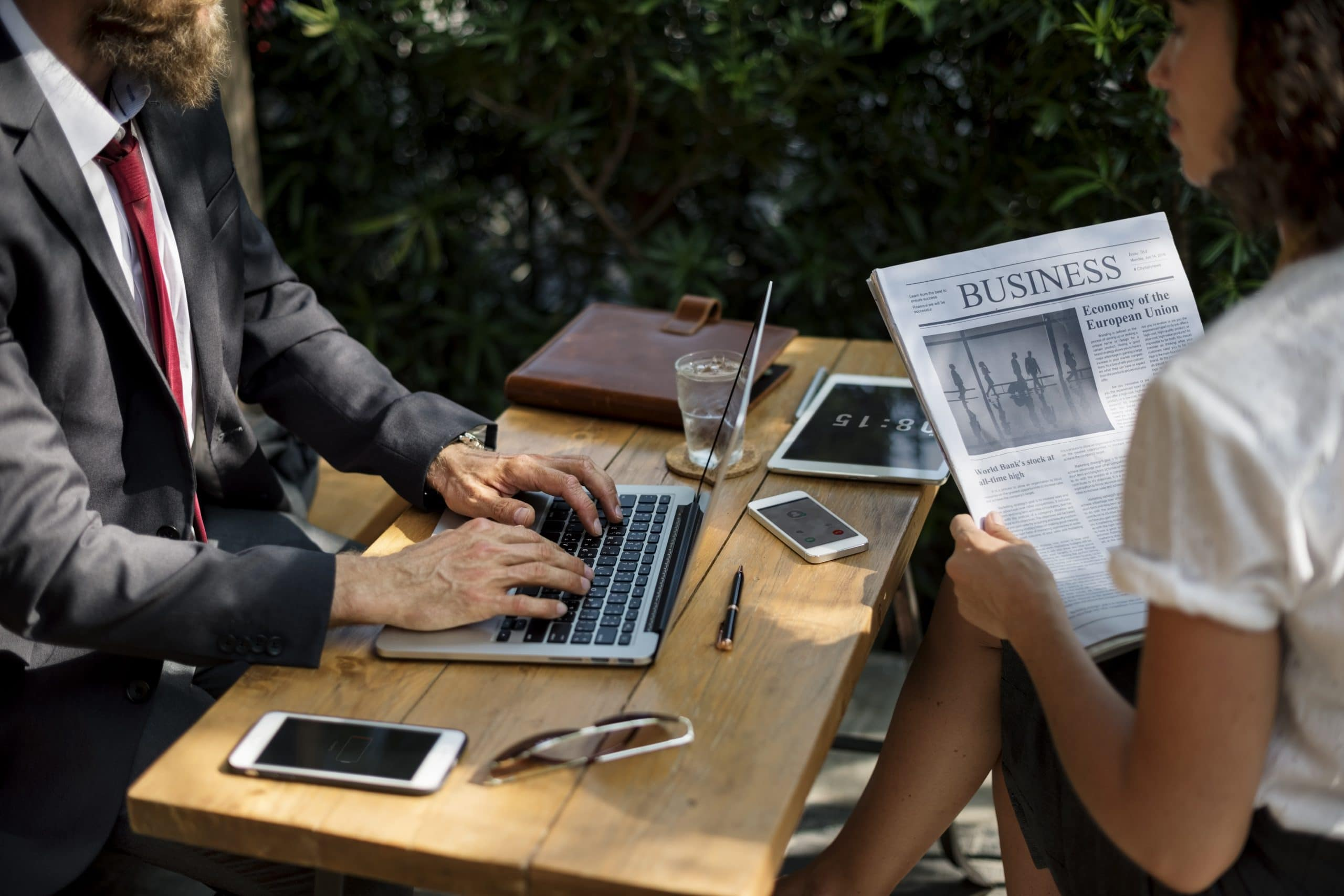 man with laptop sitting with woman reading business paper outside